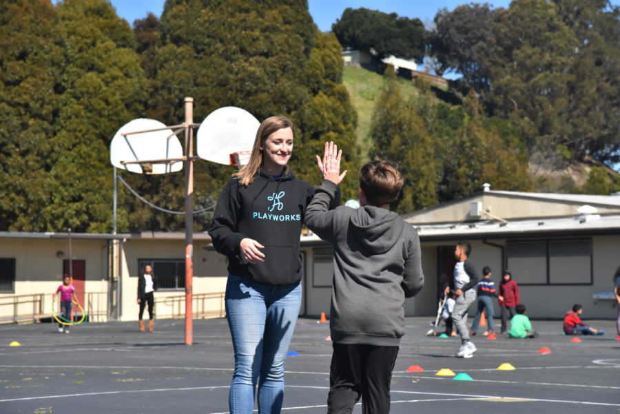 image of Playworks coach giving student high five